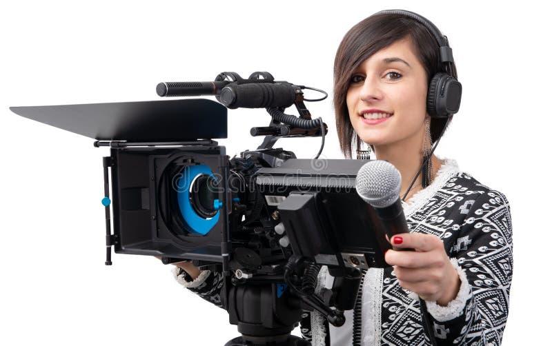 有话筒的俏丽的年轻女人新闻工作者在白色的电视演播室 库存图片