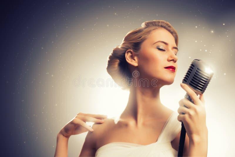 有话筒的可爱的女歌手 免版税库存图片