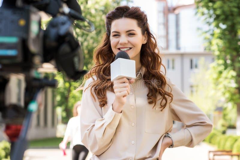 有话筒的可爱的微笑的女性新闻工作者谈话与数字式 免版税库存图片