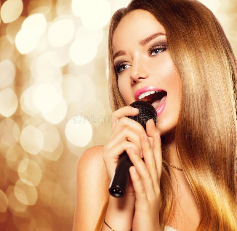 有话筒的唱歌的十几岁的女孩 卡拉OK演唱党 免版税库存图片