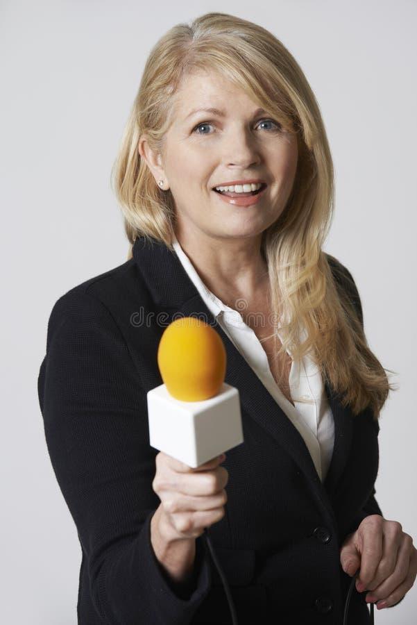 有话筒的女性新闻工作者在白色背景 库存照片
