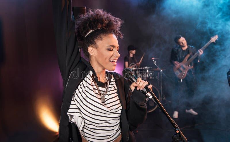 有话筒的女歌手和执行硬岩音乐的摇滚乐队 免版税库存图片