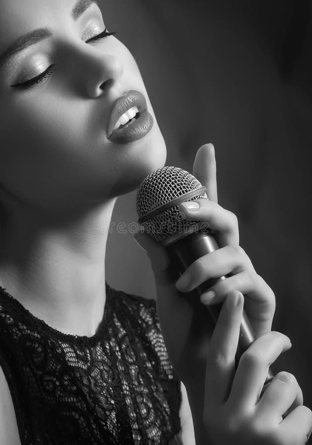 有话筒的妇女歌唱家 免版税库存图片