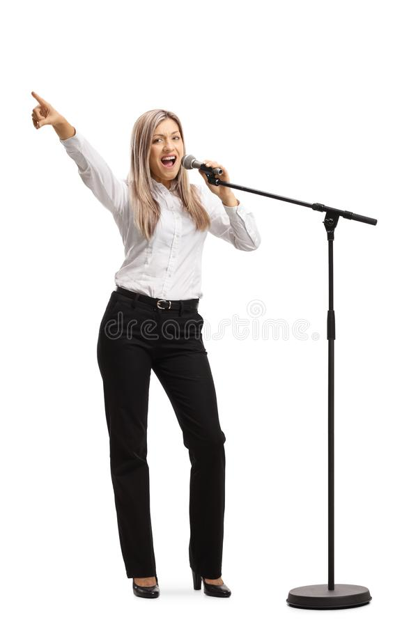 有话筒的年轻白肤金发的妇女打手势与手指的 免版税库存图片