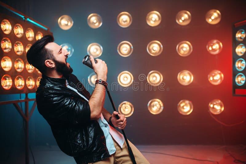 有话筒的残酷有胡子的歌手在阶段 免版税库存照片