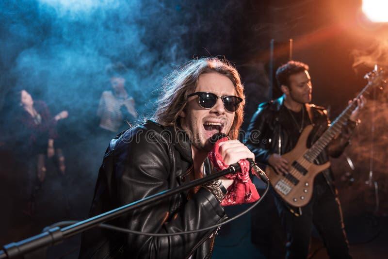 有话筒的男性歌手和执行硬岩音乐的摇滚乐队 免版税图库摄影