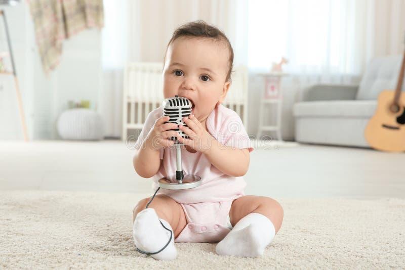 有话筒的逗人喜爱的矮小的婴孩 免版税图库摄影