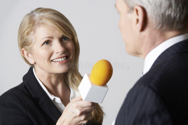 有话筒采访的商人的女性新闻工作者 库存图片