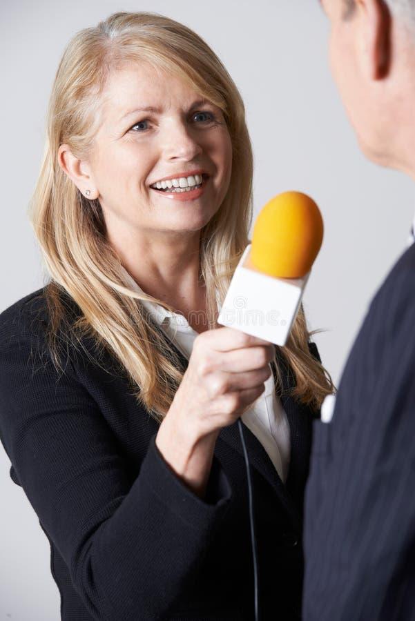 有话筒采访的商人的女性新闻工作者 库存照片