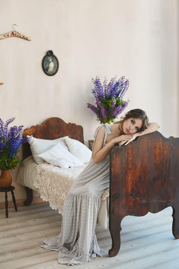 有诱人的充分的嘴唇的美丽的深色的式样女孩在时髦的礼服坐葡萄酒床在古老意大利语 免版税库存照片