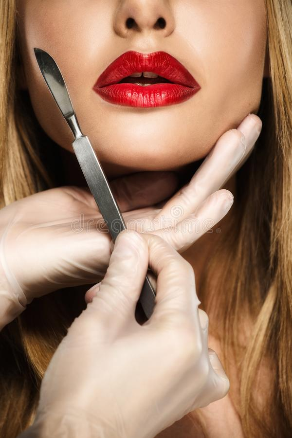 有诱人的嘴唇和解剖刀的妇女 免版税库存照片