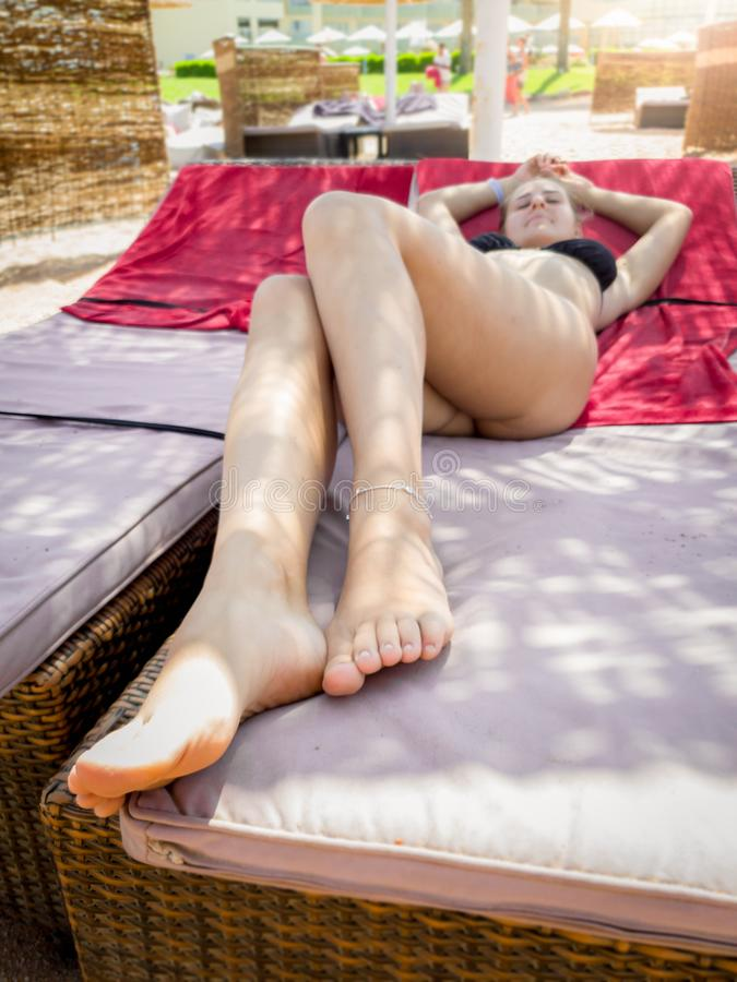 有说谎和放松在太阳床上的长的腿的美丽的年轻女人在海海滩 库存图片
