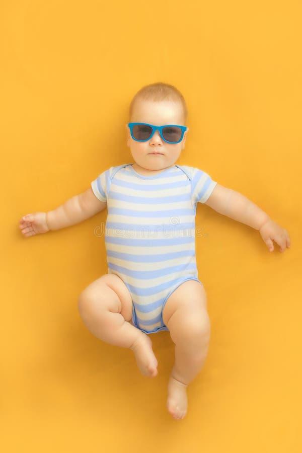 有说谎在与蓝色和白色条纹的橙色礼服佩带的小水手服和享受晒日光浴的太阳镜的逗人喜爱的婴孩 免版税库存图片