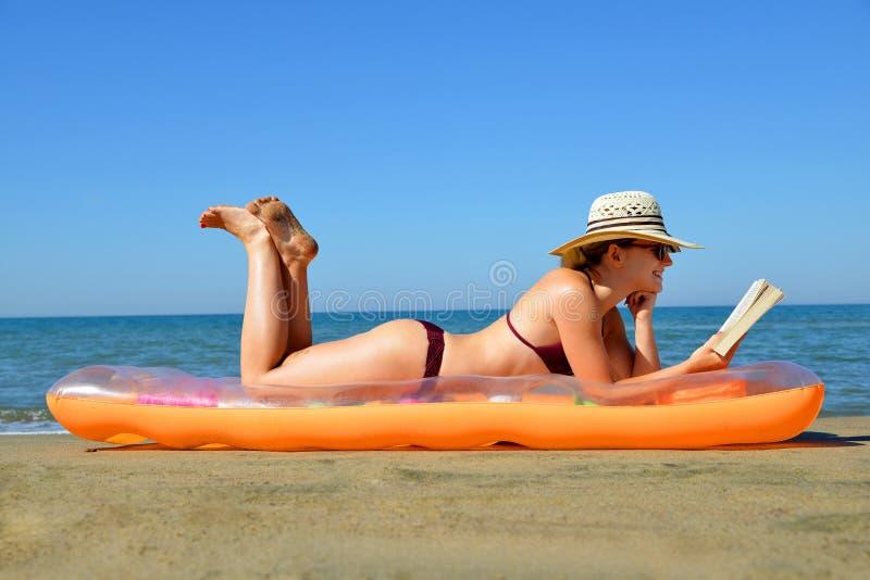 有说谎在可膨胀的床垫和读书的帽子的白种人女孩在海滩 免版税图库摄影