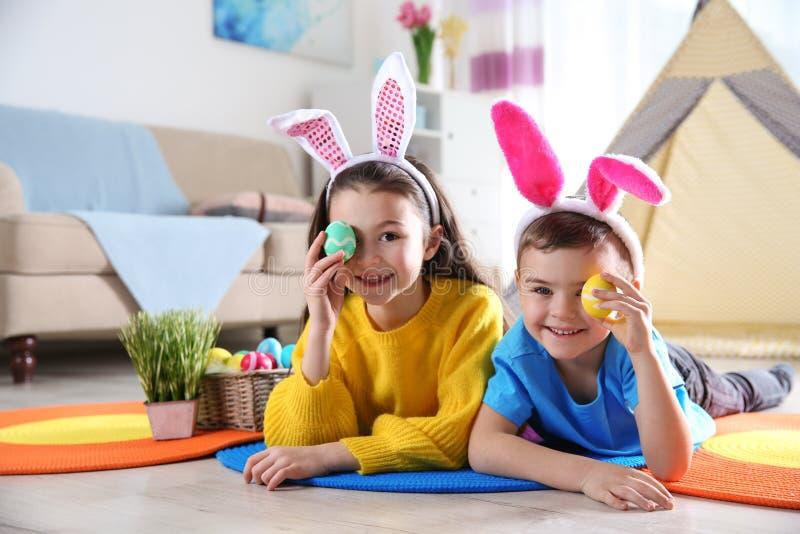 有说谎在地板上的兔宝宝头饰带和被绘的复活节彩蛋的逗人喜爱的孩子 免版税库存图片