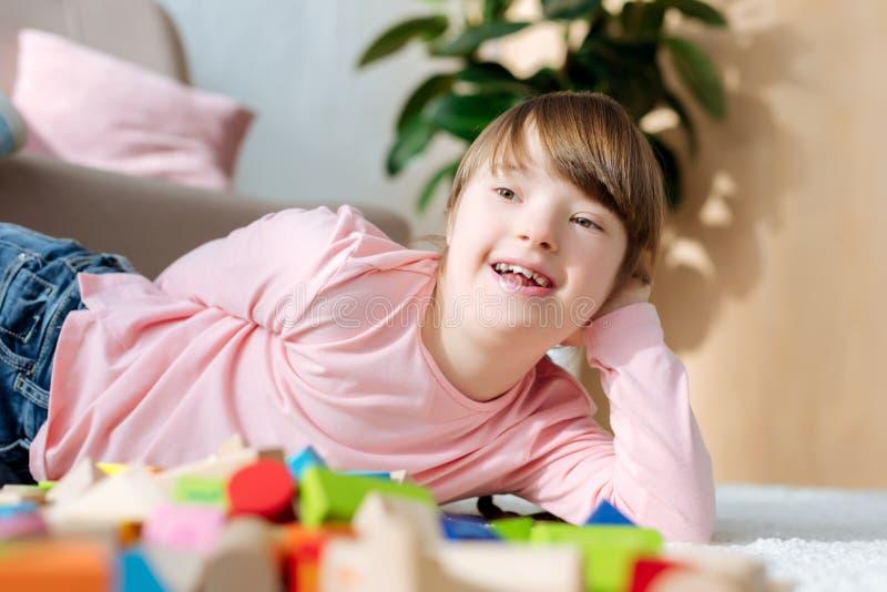 有说谎在地板上的唐氏综合症的孩子 免版税图库摄影