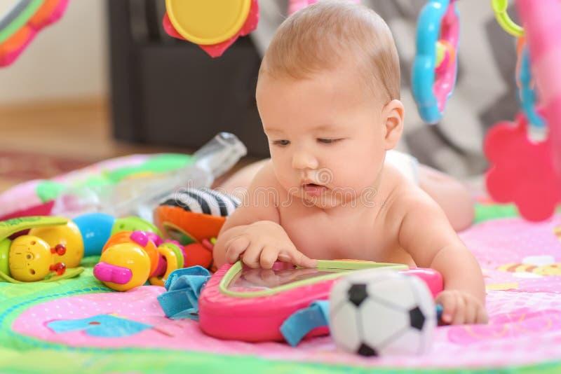 有说谎在床上的玩具的逗人喜爱的矮小的婴孩 免版税库存照片