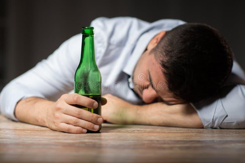 有说谎在桌上的啤酒瓶的醉酒的人在晚上 免版税库存图片