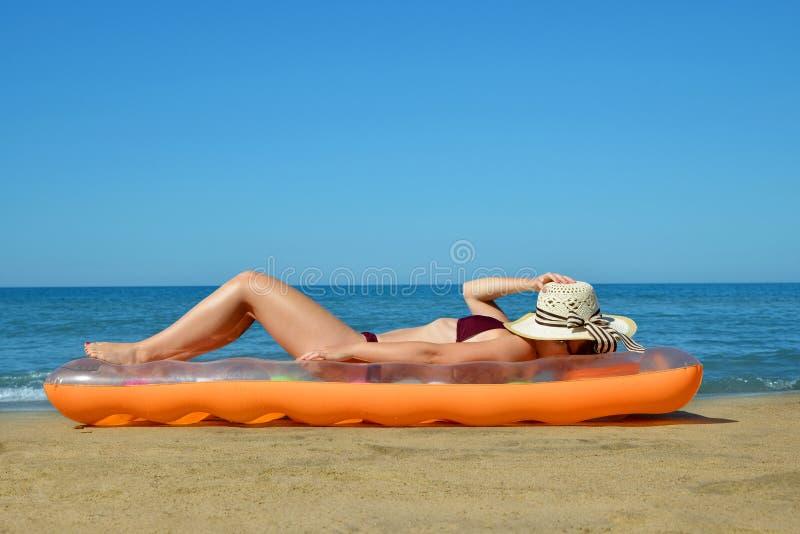 有说谎在海滩的可膨胀的床垫的帽子的白种人女孩 库存照片