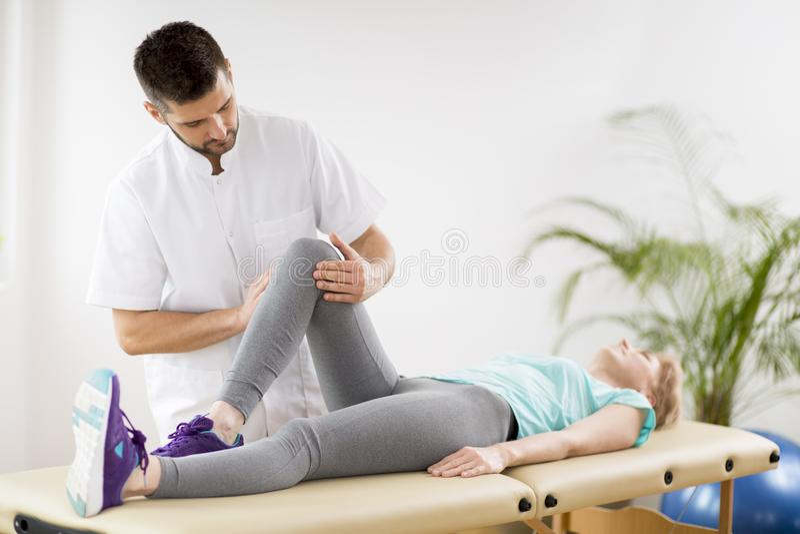 有说谎在物理疗法桌上的膝盖受伤的中年妇女在与年轻英俊的医生的会议期间 免版税库存图片