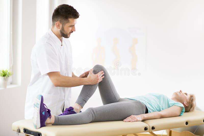 有说谎在物理疗法桌上的膝盖受伤的中年妇女在与年轻英俊的医生的会议期间 免版税库存照片