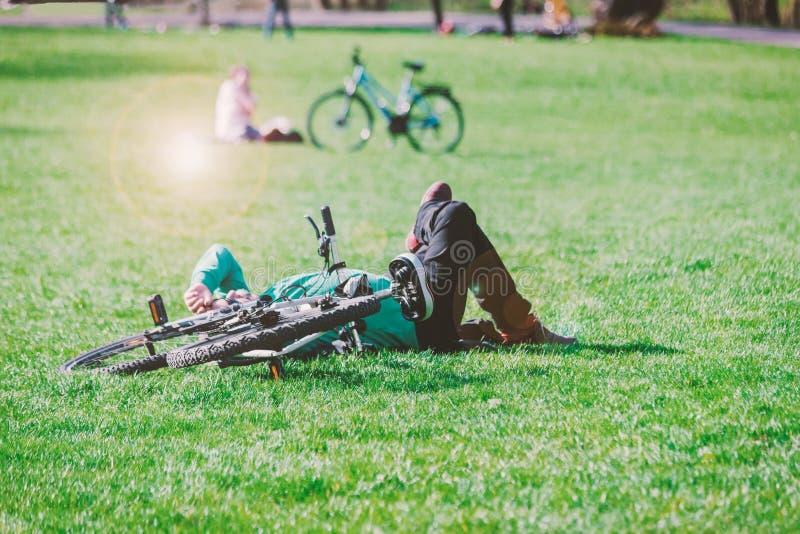 有说谎在绿草的自行车的一个人在公园 好日子,被定调子的照片 图库摄影