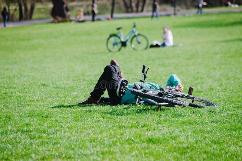 有说谎在绿草的自行车的一个人在公园 图库摄影