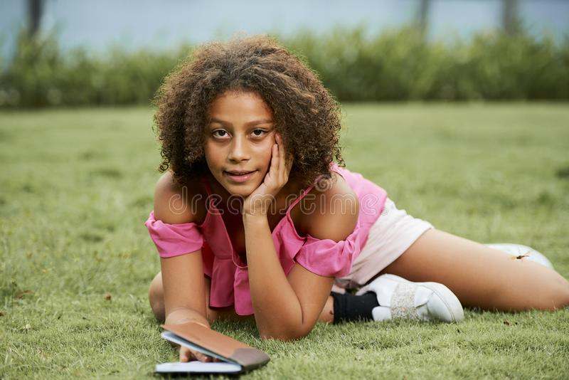 有说谎在草的日志的非洲女孩 免版税库存图片