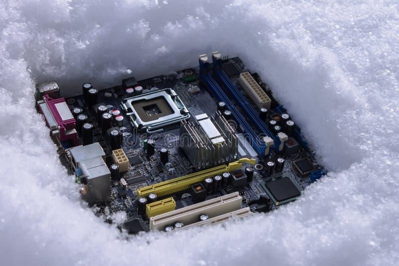 有说谎在雪的转储的处理器的一个计算机主板,扔出去的由于故障 免版税库存图片