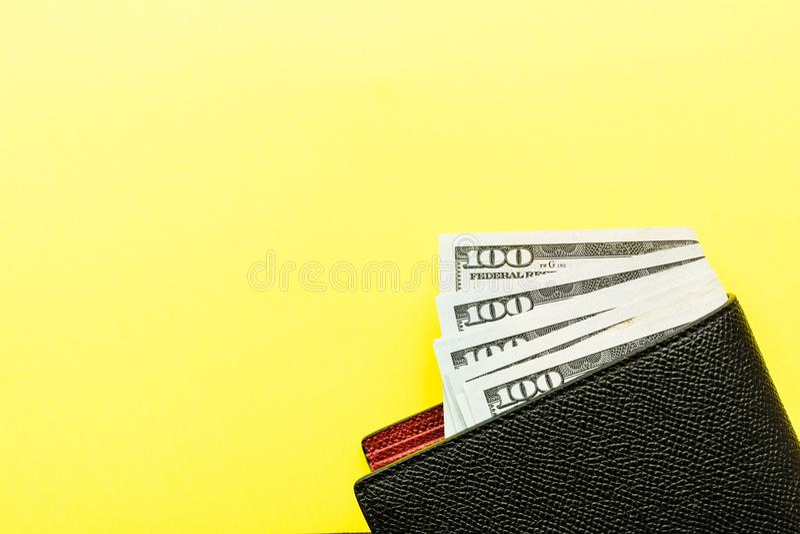 有说谎在黄色背景的一百元钞票现金的皮革钱包 财政和企业概念 r 图库摄影