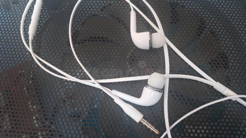 有说谎在黑背景的耳机的白色耳机 图库摄影