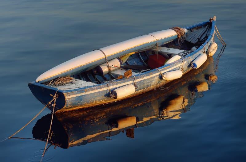 有说谎对此的皮船的一条老木小船在湖加尔达水  免版税库存照片