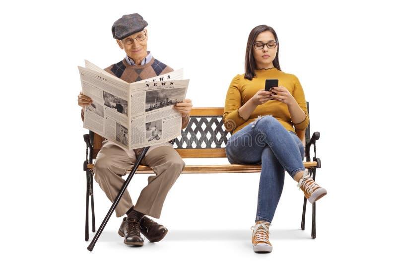 有读报纸的一个手机和一名老人的年轻女性在长凳 免版税库存图片