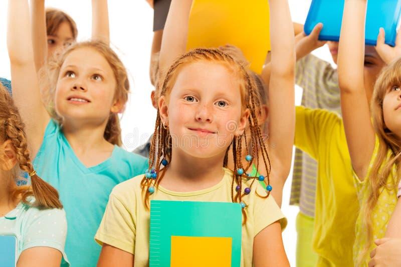 有课本的愉快的美丽的女孩在人群 免版税库存图片
