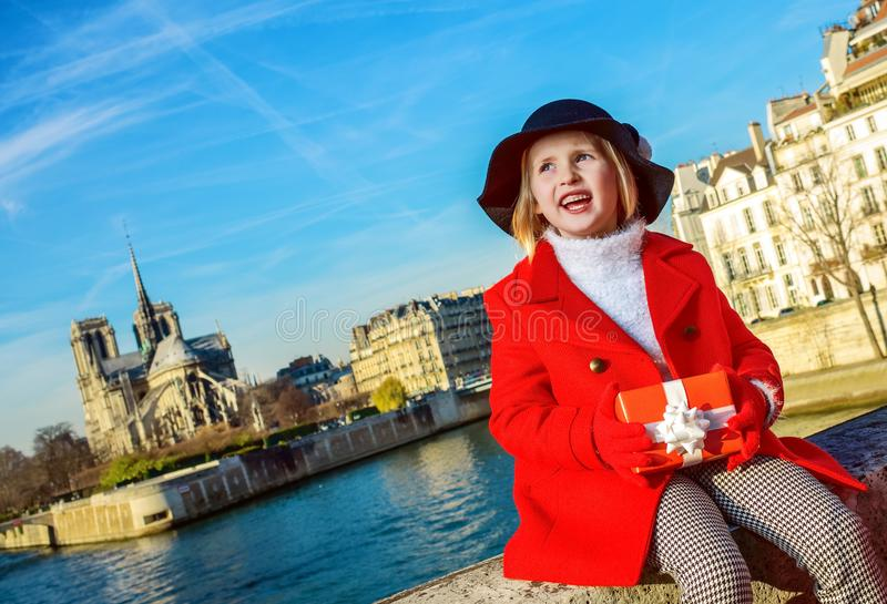 有调查距离的圣诞节礼物箱子的女孩在巴黎 免版税图库摄影