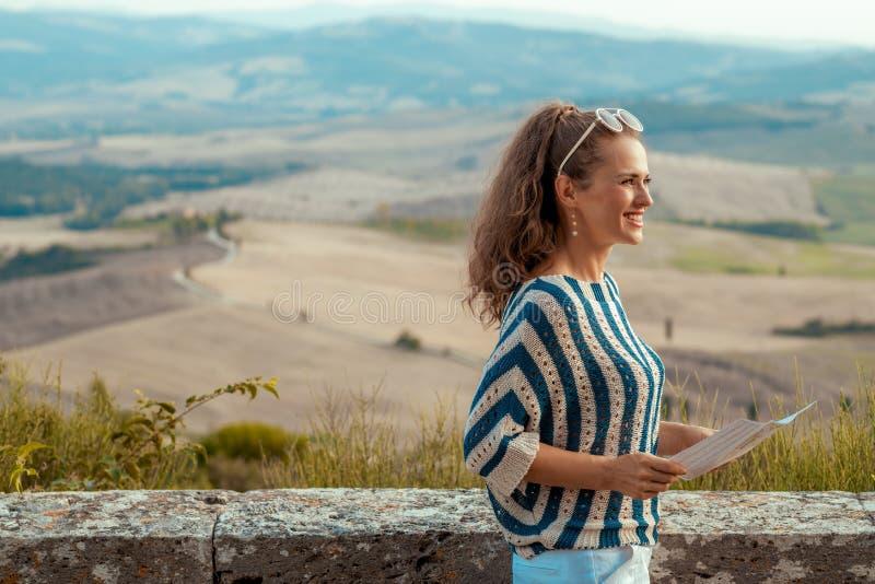 有调查距离的地图的微笑的典雅的旅游妇女 库存照片