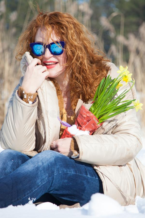 有调查距离的蓝色太阳镜的时兴的微笑的妇女,当坐在随风飘飞的雪时 库存图片