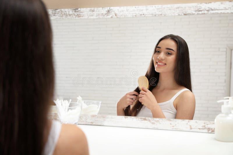 有调查镜子的发刷的美丽的年轻女人 免版税库存图片