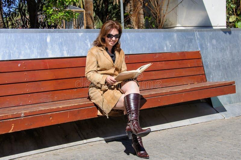 有象册的妇女在一条长凳在公园 免版税库存图片