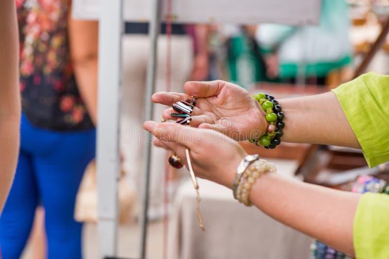有豪华卖昂贵的首饰的宝石圆环和镯子的妇女 免版税库存照片