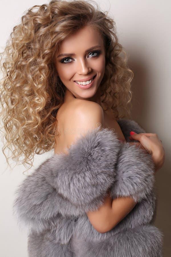 有豪华卷发的性感的美丽的女孩穿皮大衣 库存图片