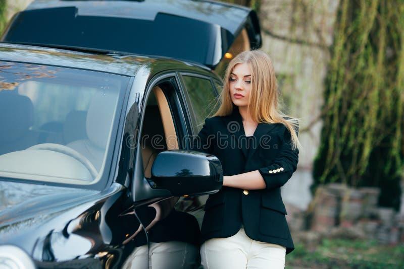 有豪华汽车的少妇 库存图片