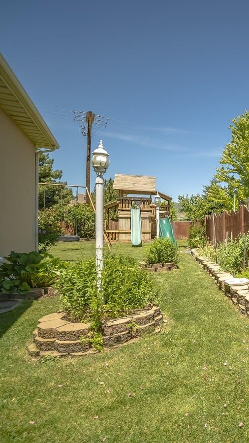 有豪华的植物和儿童的游乐场的垂直的庭院在天空蔚蓝下在一好日子 库存照片