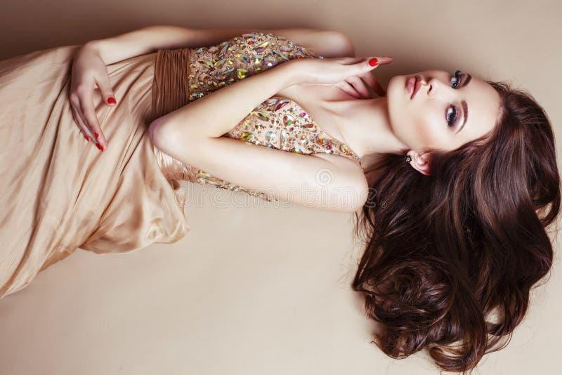 有豪华黑发的美丽的女孩在摆在演播室的衣服饰物之小金属片礼服 免版税库存图片