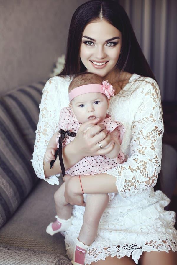 有豪华黑发的美丽的母亲和她的小婴孩 免版税图库摄影