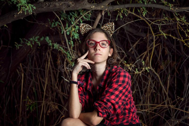 有豹子耳朵的青少年的女孩在T前面沉思地坐 库存照片