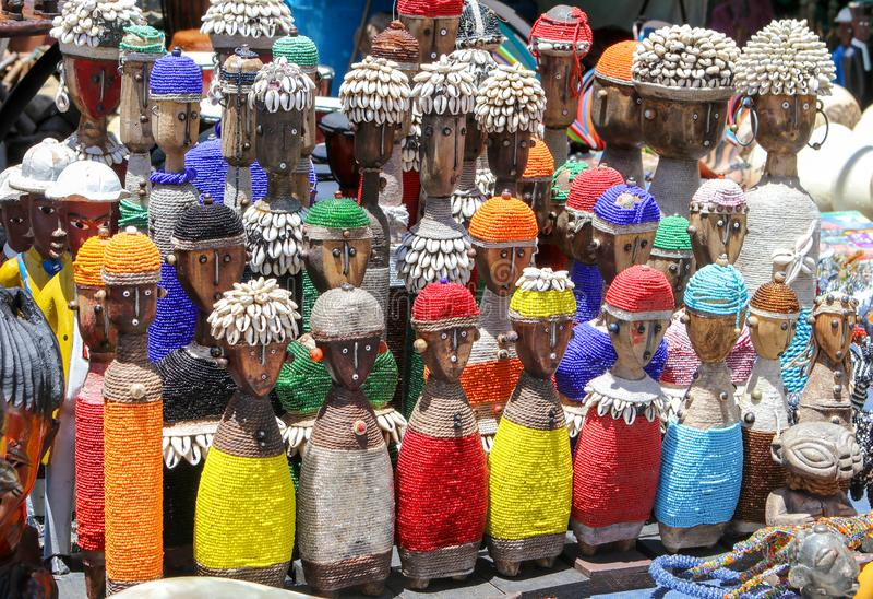 有贝壳的传统非洲木手工制造玩偶和五颜六色的小珠装饰在地方工艺市场,开普敦,南Afri上 库存图片