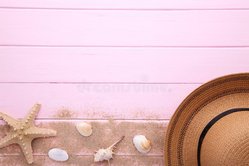 有贝壳的海滩帽子在桃红色木桌上 免版税库存照片