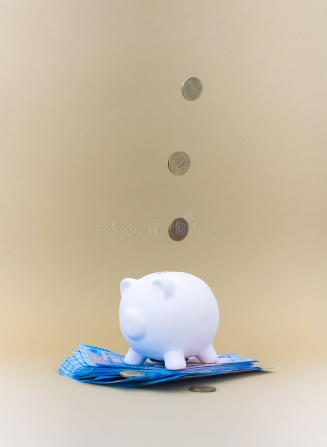 有货币和硬币的存钱罐 库存图片