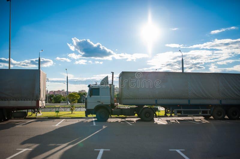 有货物拖车的一辆白色半卡车乘坐入停车场和停放与其他车 在卸载物品的无盖货车 免版税库存图片